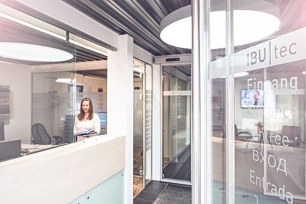 Reception and welcome room of IBU-tec in Weimar with a receptionist and a invitingly open door