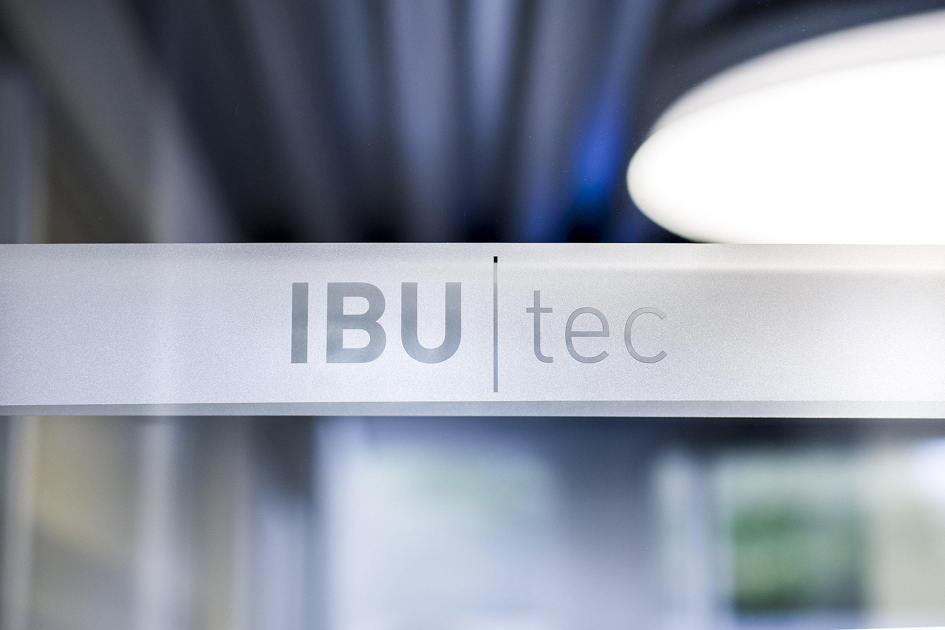 IBU-tec Logo with beautiful artsy lights in the background: blue, grey and white. Some green