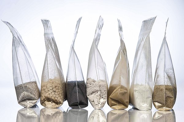 Material samples from IBU-tec production or development in bags: quartz, activated carbon and charcoal and others